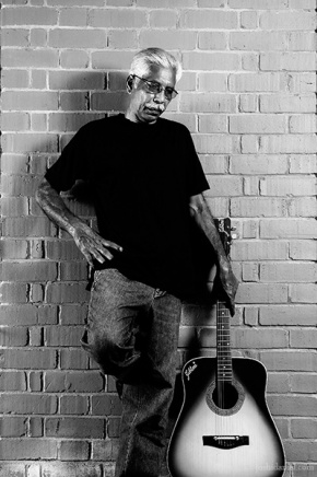Black and white portrait of an old man with guitar