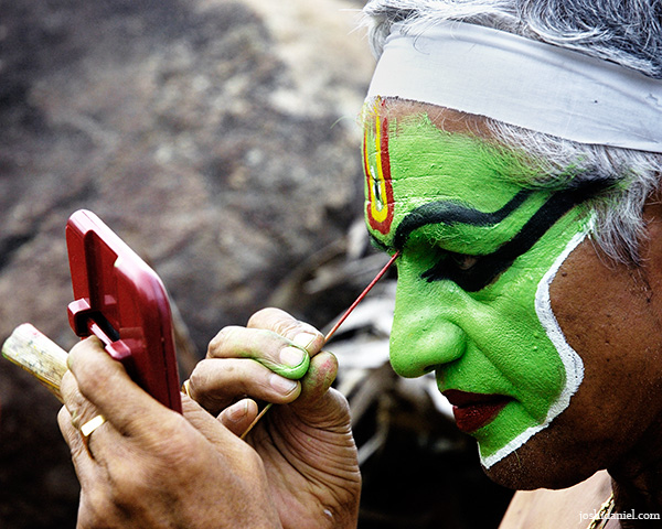 Portrait of Ottam Thullal artist Kalamandalam Prabhakaran doing make-up