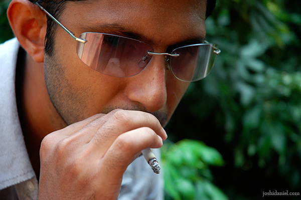 Outdoor portrait of male model Siddharth Reghunath smoking a cigarette