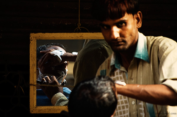 A roadside barber at work in Chor Bazaar, Mumbai, India