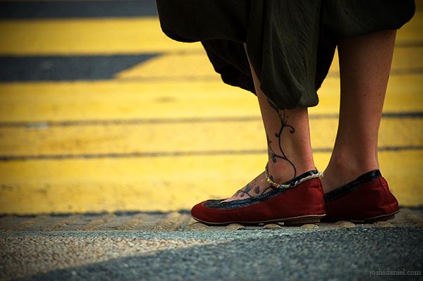 Girl with tattooed leg waiting to cross the road in Bukit Bintang, Kuala Lumpur, Malaysia