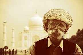 Portrait of a happy old man with turban and a long mustache sitting in front of Taj Mahal