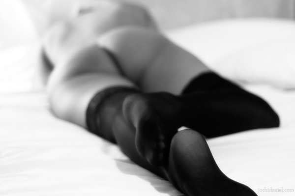 Black and white fine art nude of a girl lying on the bed