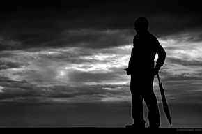 Silhouette of a man with umbrella on a cloudy day at Marine Drive, Mumbai, India