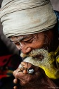 smile of a sadhu with chillum during kumbh mela 2010 in haridwar