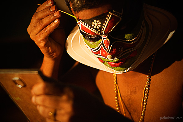 A kathakali artist doing make-up