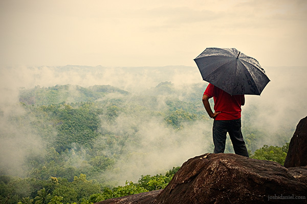 Man with umbrella standing top hill enjoying the beauty of nature
