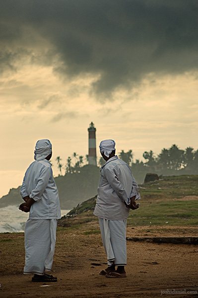 Two men looking at passing dark clouds over lighthouse in Vizhinjam, Trivandrum