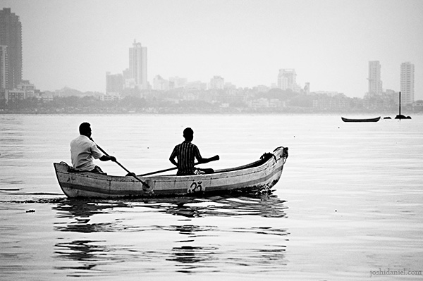 Two fishermen in boat wading through the waters near Mahim in Mumbai