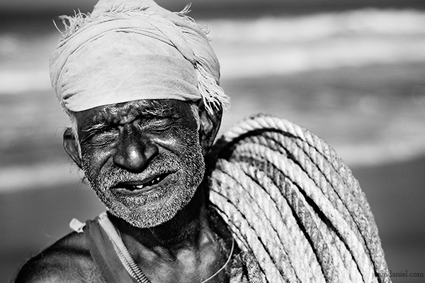 A fisherman with rope on his shoulders at Shankhumugham beach, Trivandrum