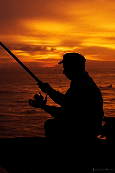 Silhouette of a man fishing at Valiathura pier at twilight