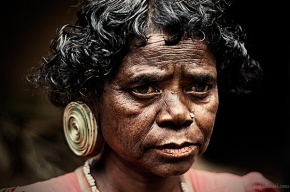 Portrait of a paniya woman with a large ear plug from Wayanad