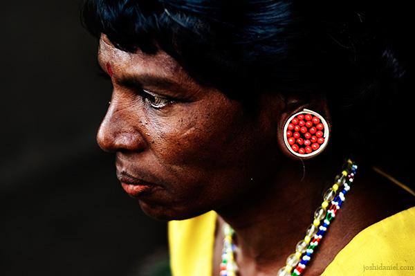 Portrait of a paniya woman with ear plug made of manjadikkuru (circassian seed)