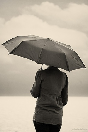 A girl with an umbrella waiting in silence in Shankhumugham beach, Trivandrum