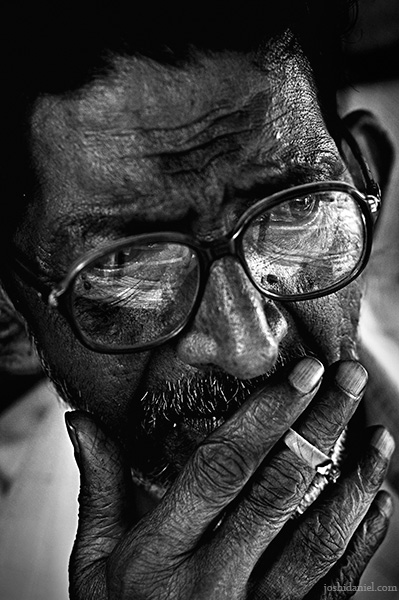 Black and white portrait of an old man with spectacles smoking beedi