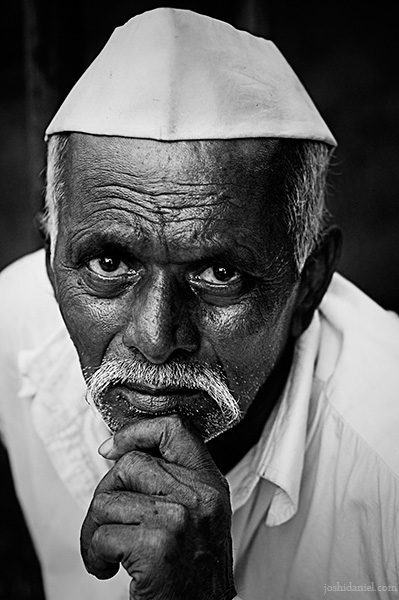 Black and white portrait of a Marathi man with topi holding his chin