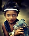 Portrait of little girl from Tamil Nadu with her puppy