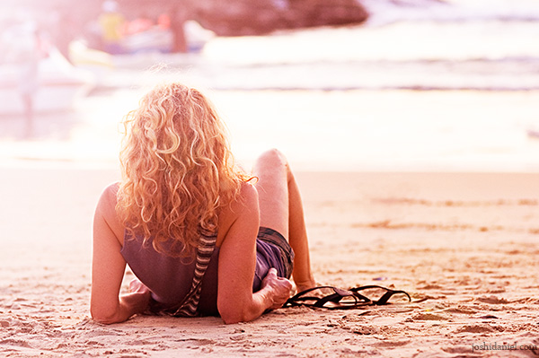 A relaxed curly haired tourist girl sitting at Kovalam Beach in Kerala