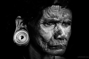 Black and white portrait of a tribal woman with a large ear plug from Wayanad in Kerala