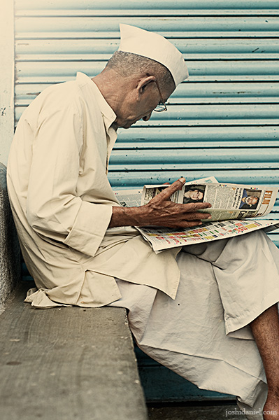 Marathi man with topi reading newspaper
