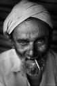 Black and white smiling portrait of an old man with beedi form Kannur