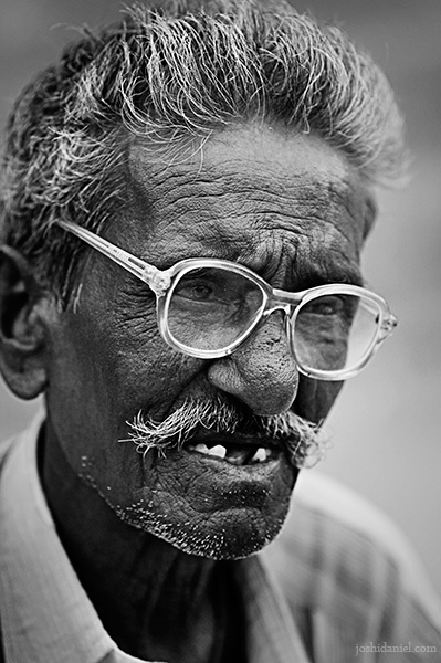 Black and white street portrait of an old man with spectacles form Kanyakumari