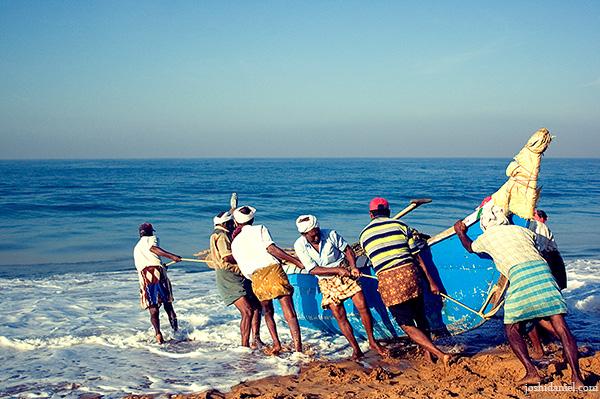 Fishermen taking the boat to sea at Shankhumugham