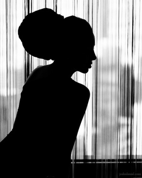 Silhouette of a girl sitting near a window