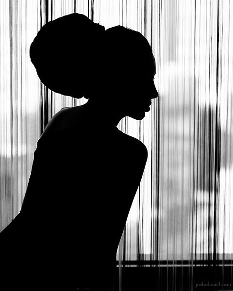 Silhouette of a girl sitting near a window