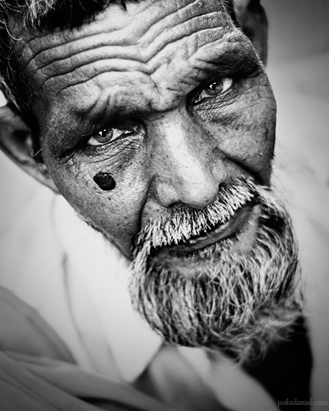 Black and white portrait of an old man with beard looking up from Mumbai