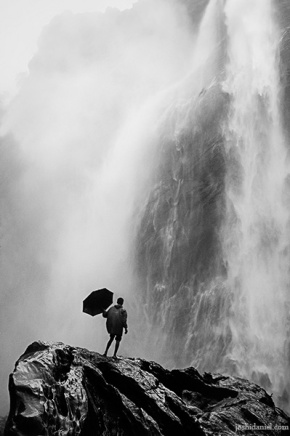 A man with umbrella standing under a waterfall