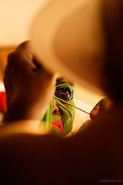 Reflection of kathakali artist Kalamandalam Gopi doing make-up