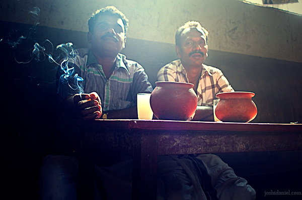 Two men with glasses of toddy behind a swirl of cigarette smoke in a kallu shap in Kozhikode, Kerala