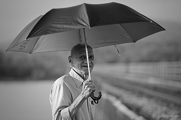 Black and white portrait of a beaming old man holding an umbrella from Kumta in Karnataka