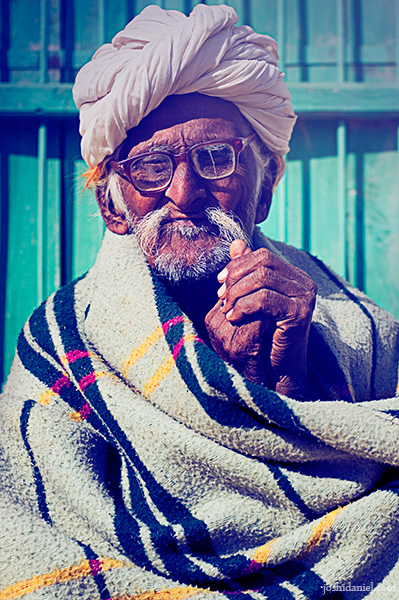 Portrait of an old bespectacled man in a turban wrapped in warm clothing from Rajasthan
