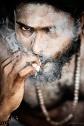 Portrait of Abilash Thankan engulfed in swirls of cigarette smoke