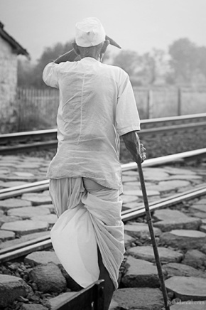 Black and white photograph of an old Maharashtrian man walking across railway tracks in Pune, Maharashtra