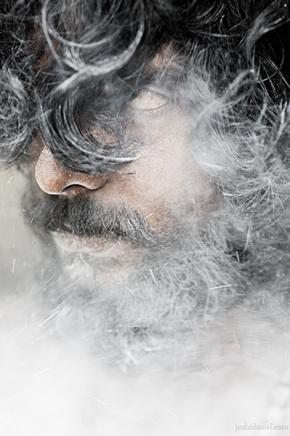 Portrait of Abilash Thankan peering through ash smeared hair
