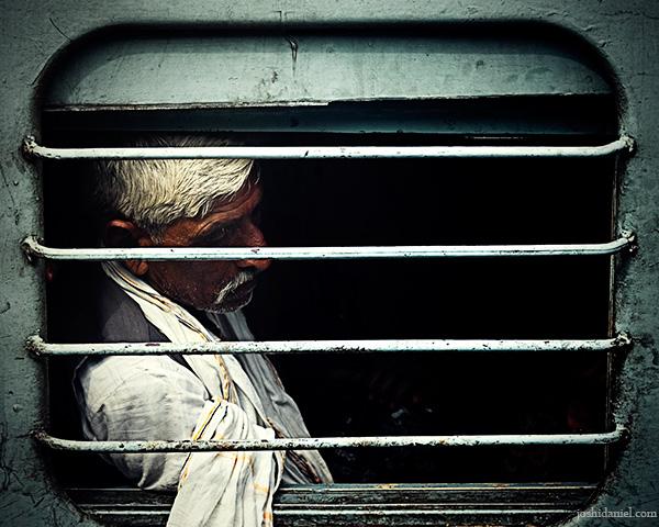 Portrait of a Maha Kumbh Mela pilgrim in Allahabad through a train window