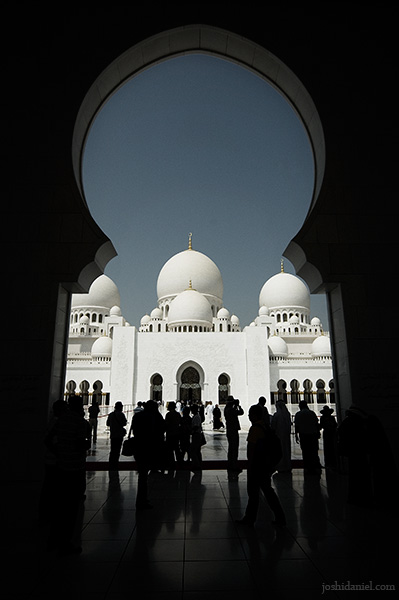 Silhouette of visitors through the arch of Sheikh Zayed Grand Mosque in Abu Dhabi