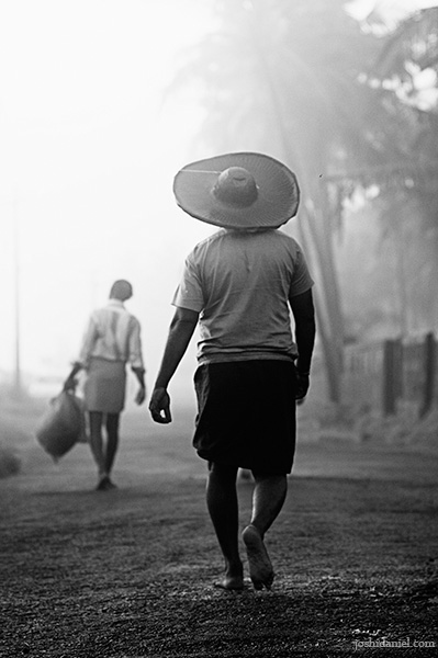Black and white photograph of a fisherman walking from Kannur, India