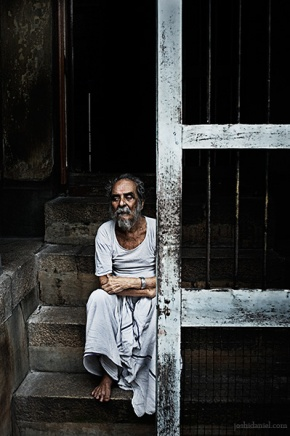 Portrait of an old man sitting on a staircase behind a door in Trivandrum, Kerala
