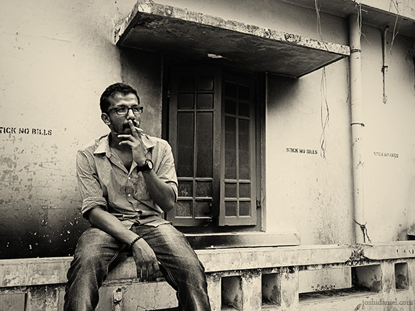 Black and white portrait of Chandrakanth C K smoking cigarette