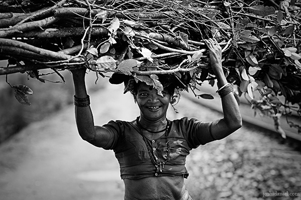 Black and white photograph of a smiling woman carrying fire wood on her head in Kumta, Karnataka