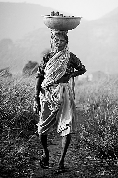 Black and white photograph of a an old woman carrying a load on her head in Pune