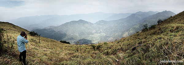A panoramic image of Kiran Syam taking a photograph of Ponmudi hills in Kerala