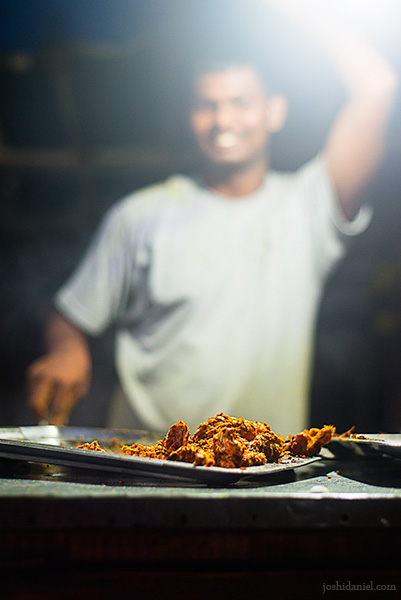 A smiling young man frying crabs at Elliot's Beach, Chennai