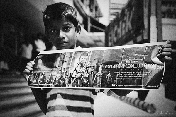 Black and white portrait of a boy holding a Kochadaiiyaan movie poster starring Rajinikanth at Udhayam theatre in Chennai
