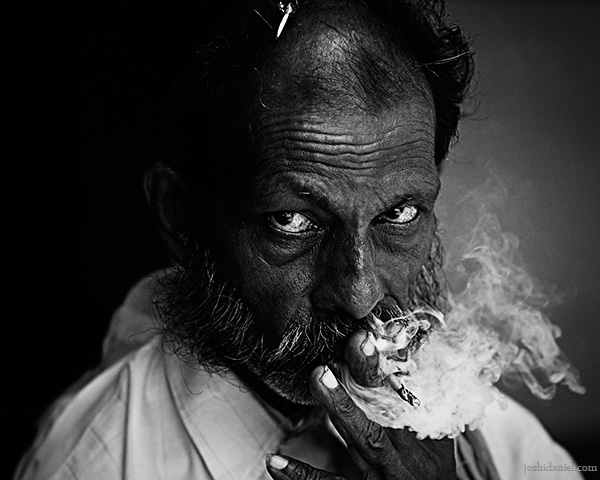 Black and white portrait of an intriguing man from Gokarna smoking