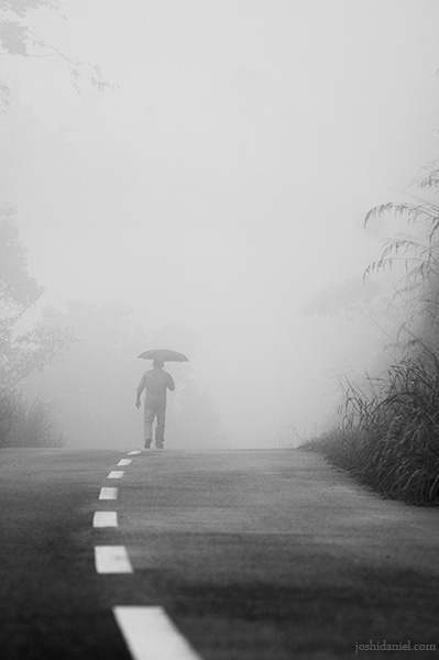 Black and white conceptual photograph of a man holding an umbrella walking on a foggy road in Ponmudi, Kerala